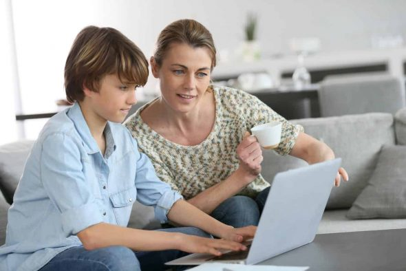 Mother teaching son about kids internet safety on laptop